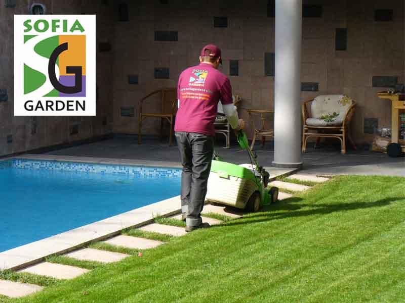 Косене на трева в градина с моторна косачка